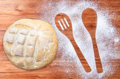 Wooden brown table dusted with flour and loaf of wheat bread. Silhouette two spoons of flour. Wooden brown table dusted with flour and a loaf of wheat bread stock photo