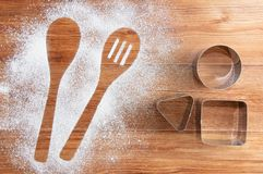 Wooden brown table dusted with flour and metal tins. Silhouette a two spoons of flour. Wooden brown table dusted with flour and metal tins. Silhouette two spoons stock images