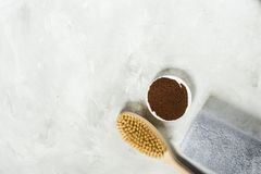 Wooden brush for dry massage and ground coffee with a towel. View from above stock image