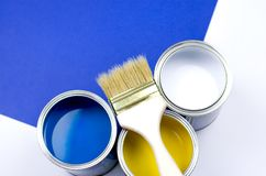 Wooden brush with three multi-colored cans of paint stock image