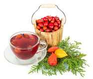 Wooden bucket with berries  wild rose and cup  tea isolated. Stock Photography
