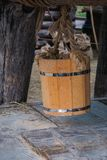 Wooden bucket hanging over groundwater well. Close up of wooden bucket hanging from log over groundwater well royalty free stock photos