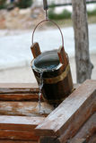 Wooden bucket over the well with flowing water Stock Photo