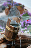 Wooden bucket over the well with flowing water and cobwebs Royalty Free Stock Photography