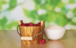 Wooden bucket of ripe fragrant raspberries. And a cup of sugar on a table Royalty Free Stock Photos