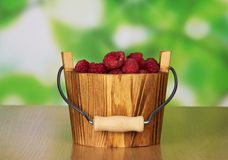 Wooden bucket of ripe fragrant raspberries. On a table Stock Image