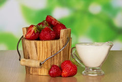 Wooden bucket with strawberries and cup cream on abstract green. Royalty Free Stock Image