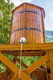 Wooden bucket with water running from faucet Royalty Free Stock Photos