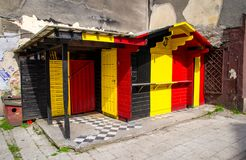 Wooden building with Belgium and Germany flag colors. Wooden building with combination of Belgium Belgien and Germany Deutschland flag colors: black, red, yellow stock image