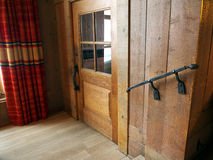 Wooden building interior. Rustic wooden building interior, with glass door wrought iron rail and red curtain Stock Images
