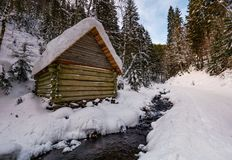 Wooden building near the stream in snowy forest. Lovely winter scenery, great place for hiking in fine weather Stock Photography