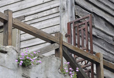 Wooden building in old style. Old wooden building with wooden handrail and iron door, full of rust Royalty Free Stock Images