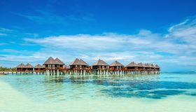 Wooden bungalow on the background of azure water and blue sky, Maldives Stock Photo