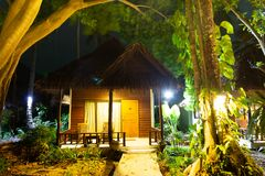 Wooden bungalow in the forest. House at night in the jungle. Tall green tropical trees in the foreground, in the background a. Starry sky royalty free stock photography