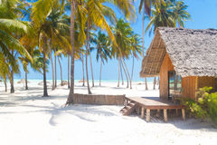 Wooden bungalow on tropical white sandy beach Royalty Free Stock Images