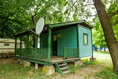 Wooden bungalows on campsite are in shade of green trees. Stock Images