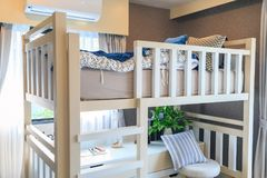A wooden bunk bed with a pillow and air conditioner in a childre. A white wooden bunk bed with a pillow and air conditioner in a children`s bedroom with warm Royalty Free Stock Photos