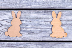 Wooden bunnies on grey background. Cutout animal figurines. Animalistic elements of decor royalty free stock photo