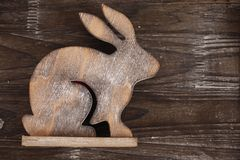 Wooden bunny on wooden background. Wooden bunny on dark wooden background Royalty Free Stock Images