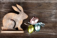 Wooden bunny on wooden background. Wooden bunny on dark wooden background with easter eggs stock photography
