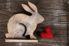 Wooden bunny on wooden background. Wooden bunny on dark wooden background with red heart Stock Photos
