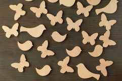 Wooden butterflies and birds on a black wooden background Royalty Free Stock Photos