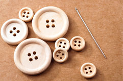Wooden buttons and a needle on brown piece of carton Royalty Free Stock Images
