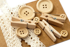 Wooden buttons, needle, pegs and white lace Royalty Free Stock Photo