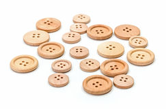 Wooden buttons on white surface Royalty Free Stock Image