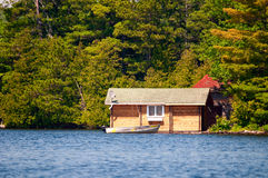 Wooden cabin and a boat Royalty Free Stock Images