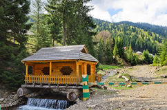 Wooden cabin built over a waterfall Stock Images