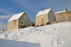 Wooden cabin and dogs in winter. Houses in the Kulusuk village, Greenland Stock Images