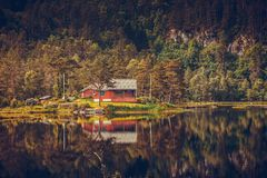 Wooden cabin in forest on lake shore, Norway Royalty Free Stock Images