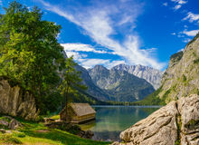 Wooden cabin on idyllic coast against alpine mountains and wonde Royalty Free Stock Images