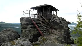 Wooden cabin on main peak of rock as view point, dark clouds in the sky. Summer early morning stock video