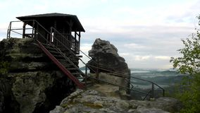 Wooden cabin on main peak of rock as view point, dark clouds in the sky. Summer early morning stock video footage