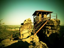 Wooden cabin on main peak of rock as view point, dark clouds in the sky. Summer morning in sandstone rocks Royalty Free Stock Images