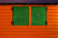 Wooden cabin painted in secondary colors. Red green purple royalty free stock photo