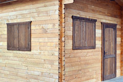 Wooden cabin timber walls joints on the corner window shutters and door Royalty Free Stock Images