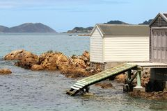 Wooden cabin on waterside with pier royalty free stock photos