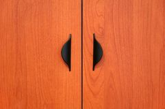 Wooden cabinet doors. With black handles stock photos