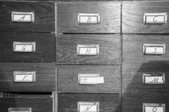 Wooden cabinet of drawers labelled with letters. Of the alphabet in a close up view in a storage and organisation concept royalty free stock photography