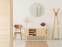 Wooden cabinet with flowers between stylish brown chair and wooden hanger royalty free stock photo