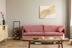 Wooden cabinet and log of wood next to pink couch in elegant living room interior stock image