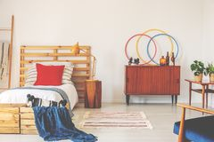 Wooden cabinet next to bed with red cushion and blue blanket in retro bedroom interior. Real photo. Concept stock images