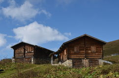 Wooden cabins in Black Sea Region. Two traditional wooden cottages or cabins with closed shutters on a grassy hillside in the Black Sea Region,  blue sky and Stock Photo