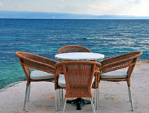 Wooden cafe chairs and table in front of the sea Royalty Free Stock Images