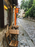 Wooden cafe table and chairs squeezed onto narrow sidewalk in Paris, France Stock Photos