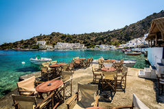 Wooden cafe tables at pier of Loutro town on Crete island, Greece Stock Photo