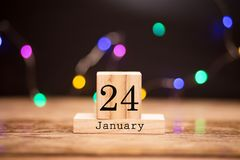 Wooden calendar with black 24 january word at center of dark background with garland bokeh. Winter time, year concept royalty free stock images